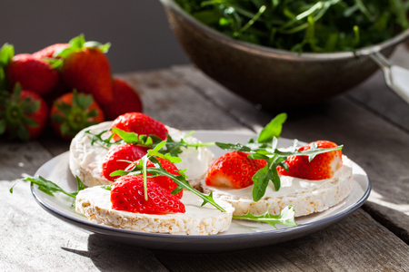 mascarpone: Multigrain rice cakes with strawberries fruit , soft mascarpone cheese and arugula for healthy breakfast. Stock Photo