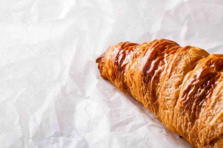 pasteleria francesa: Croissant franc�s pasteler�a en papel blanco para hornear.