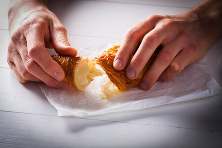 pasteleria francesa: Manos arrancan un trozo de croissant pasteler�a francesa en el papel de hornear blanco. Foto de archivo