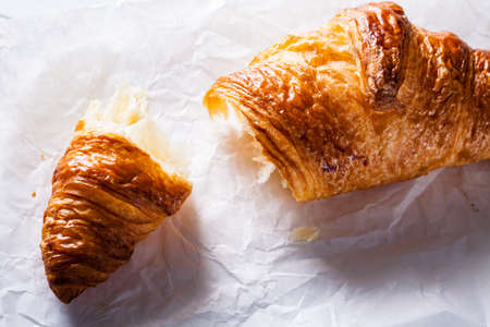 buttery: Tear off a piece of French pastry Croissant on white baking paper.