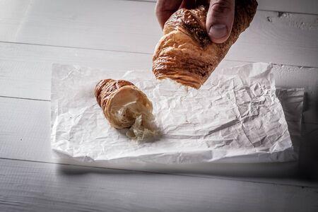 pasteleria francesa: Manos arrancan un trozo de croissant pastelería francesa en el papel de hornear blanco. Foto de archivo