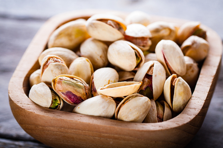 pistachios: Pistachios in wooden bowl. Stock Photo