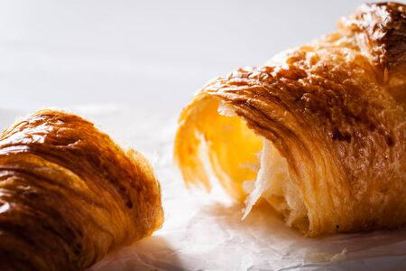 pasteleria francesa: Tear off a piece of French pastry Croissant on white baking paper.