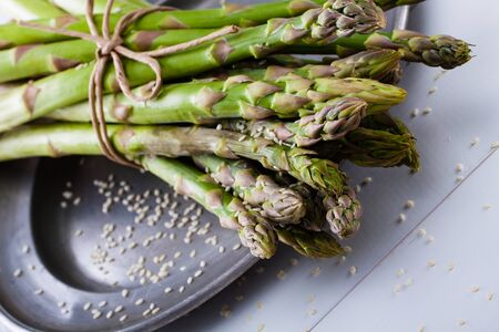 hoard: A bunch of asparagus with sesame on a rustic silver plate.