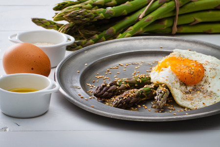 roasted sesame: Asparagus with roasted sesame and fried egg on rustic iron plate. Stock Photo