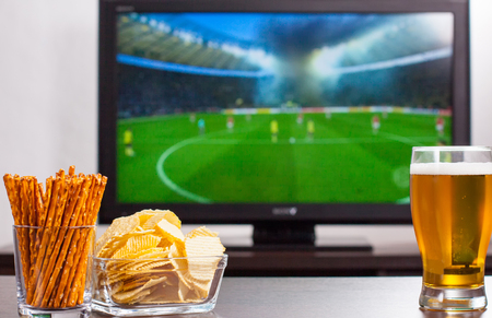 televisor: Pint of beer, chips and salty sticks on the tables in front of televisor show off football.Set of snacks and beverage soccer fan at home.