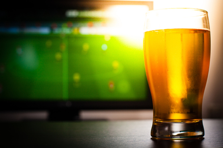 televisor: Pint of beer on the tables in front of televisor show off football. Stock Photo
