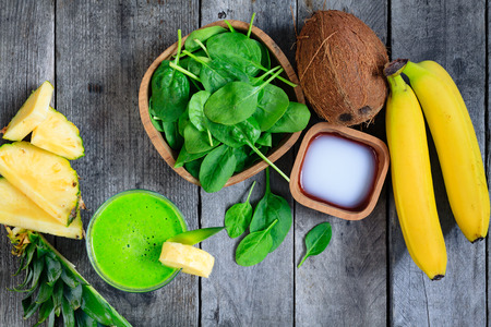 A glass of green smoothies, and the ingredients from which it was made. Smoothies with spinach, banana, coconut water, pineapple on gray wooden table.