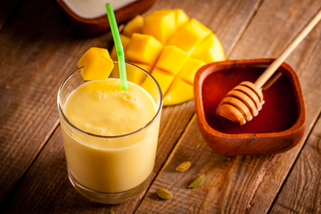 Glass of mango lassi, Indian drink made from yogurt with blended mango and honey, flavored with cardamom. Stock Photo