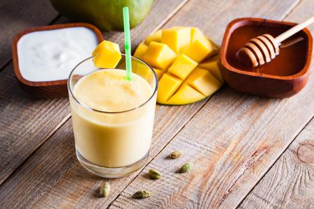 カルダモン風味のマンゴーのラッシー インド飲み物のグラス。木製の背景のミルクセーキ。