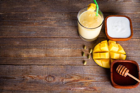 Top view of glass milkshake with mango, yoghurt and honey with copy space on wooden board.