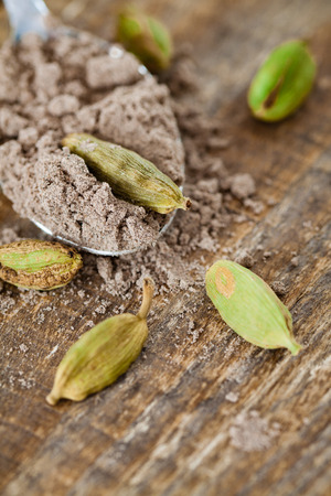 Scoop of ground cardamom pods and a wooden table. Stock Photo