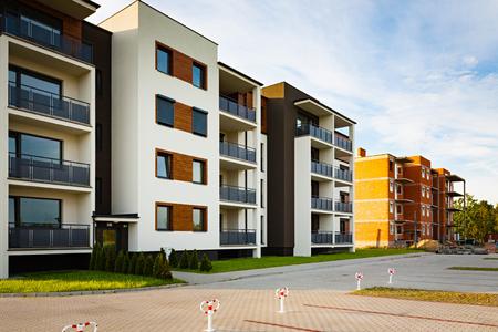 Nuevo bloque plurifamiliar con balcones y fachada brillante decorado con paneles de madera. Editorial