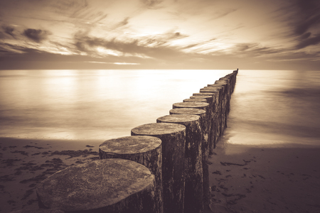 Coast with piles during sunset, long exposure blurring water.Vintage photo of baltic, Poland.