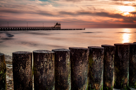 beach panorama: Coast with piles during sunset, long exposure blurring water.Baltic, Poland.