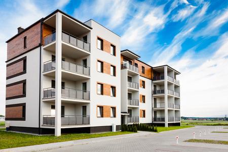Nieuwe multi-familie blok met balkons en heldere gevel versierd met houten lambrisering.