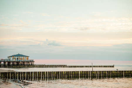 groyne: Restaurant on the water and wooden poles. Poland, Baltic, Ustronie Morskie.