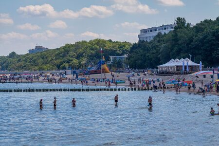 immediate: KOLOBRZEG, POLAND - JUNE 23, 2016: Many vacationers spend time on the sandy beach in the immediate vicinity of the pier by the Polish coast of the Baltic Sea.