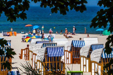 vacationers: KOLOBRZEG, POLAND - JUNE 23, 2016: Many vacationers spend time on the sandy beach, some of them sitting on wicker beach chairs. Photo framed by leaves of trees.