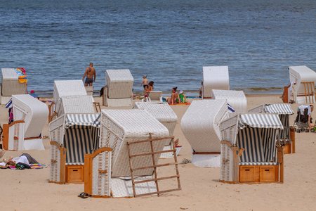 vacationers: KOLOBRZEG, POLAND - JUNE 23, 2016: Many vacationers spend time on the sandy beach, some of them sitting on wicker beach chairs. Editorial