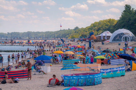 vacationers: KOLOBRZEG, POLAND - JUNE 23, 2016: Many vacationers spend time on the sandy beach in the immediate vicinity of the pier by the Polish coast of the Baltic Sea.