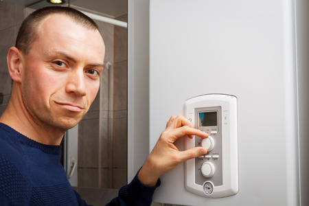 set up: Men regulate temperature on control panel of central heating or DHW at combi boiler in restroom. Stock Photo