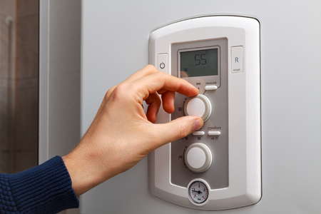 regulate: Men hand regulate temperature on 55 degree in control panel of central heating.