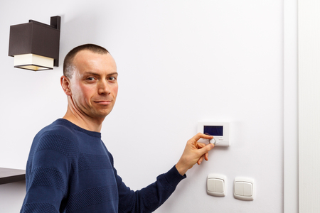 regulate: Men regulate temperature on control panel of central heating at wall in living room.