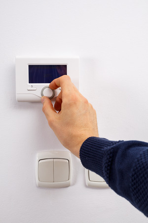 temperature controller: Men hand setting the temperature on control panel of DHW or central heating.