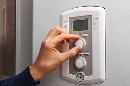 regulate: Men hand regulate temperature on 65 degree in control panel of central heating.