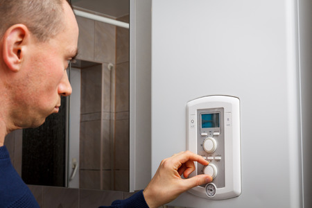 regulate: Men regulate temperature on control panel of central heating or DHW at combi boiler in restroom. Stock Photo