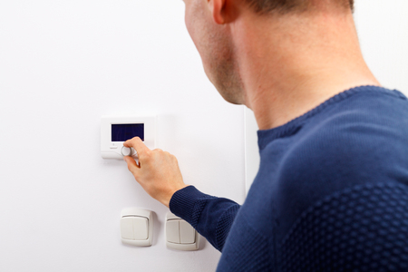 temperature controller: Men regulate temperature on control panel of central heating at wall in living room.