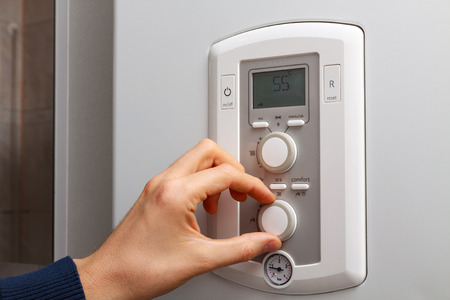regulate: Men hand regulate temperature on 55 degree in control panel of DHW. Stock Photo
