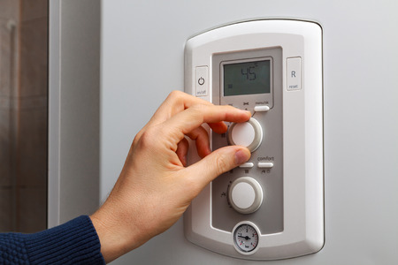 regulate: Men hand regulate temperature on 45 degree in control panel of central heating.