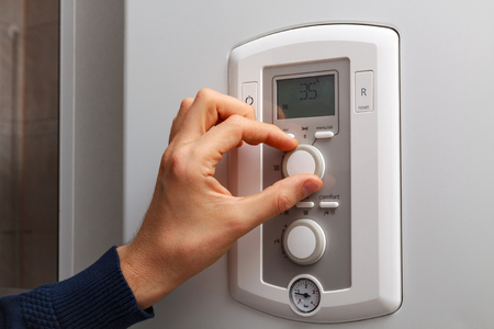 regulate: Men hand regulate low temperature on 35 degree in control panel of central heating.
