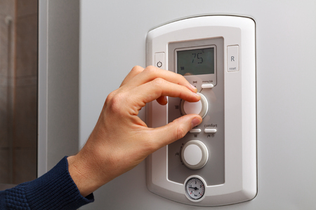 regulate: Men hand regulate high temperature on 75 degree in control panel of central heating. Stock Photo