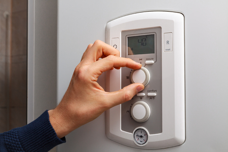regulate: Men hand regulate low temperature on 40 degree in control panel of central heating. Stock Photo