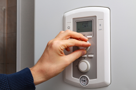 regulate: Men hand regulate temperature on 50 degree in control panel of central heating.