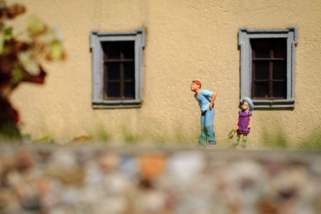 children at play: Small figurine of two children play in the garden.