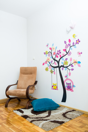 Handmade posters stuck tree with birds on the wall in childrens room.