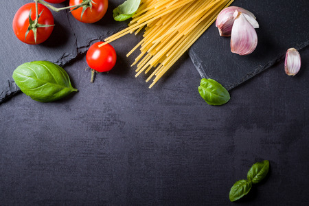 Food ingredients for Italian spaghetti on black slate stone background with much copy space of your project.