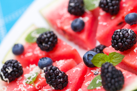 sliced watermelon: Watermelon pizza slices with fresh blueberry, blackberry, chips of white chocolate and green mint leaves.