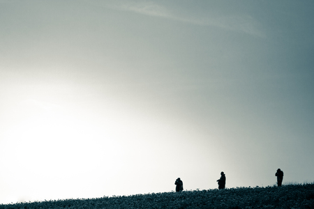 photgraphy: Three silhouettes of photographers on field horizon. Vintage style photography.