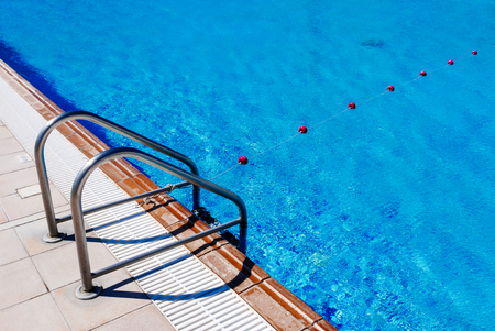 edges: Ladder of pool and rope with buoys of hotel outdoor swimming pool. Stock Photo