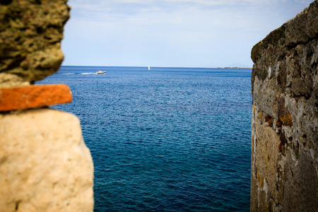 View at sea with boats through chink in the wall ancient ruins. Stock Photo