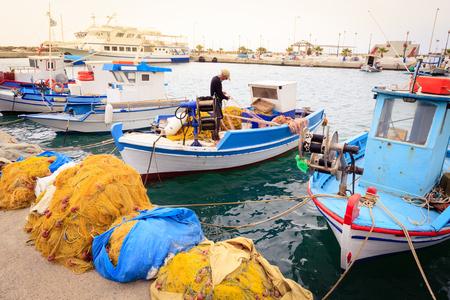 trawler net: Colorful Greek fishing boats and fisherman in port of Kardamena in Kos island, Greece.