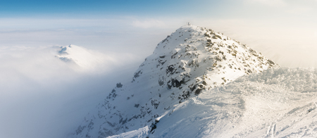 tatra: Chopok peak on snowy winter time, above the clouds with sun rays effect. Stock Photo