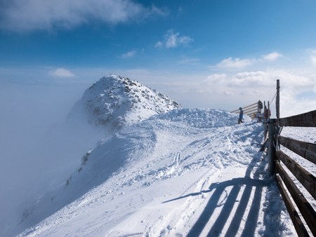 tatra: Chopok peak on snowy winter time, above the clouds with plank fence and skier on foreground.