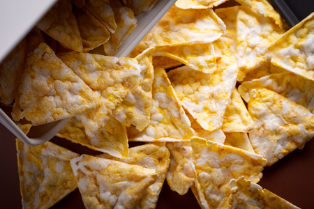 Healthy version of corn nachos scattered on glossy glass table. Stock Photo