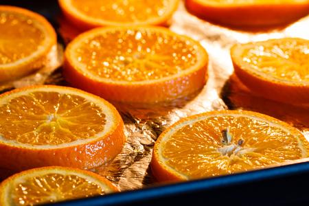 Baking fresh orange slices, to dry them for Christmas decoration. Stock Photo